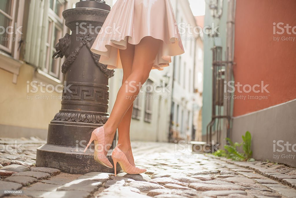 Sexy lady with beautiful legs walking in old town stock photo