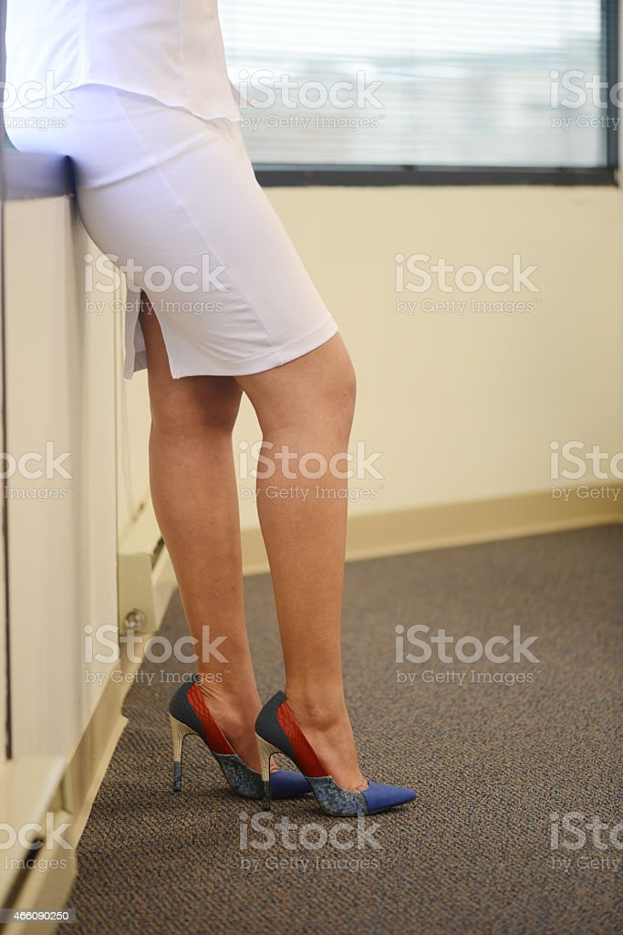 Sexy legs of a woman wearing a skirt high heels stock photo