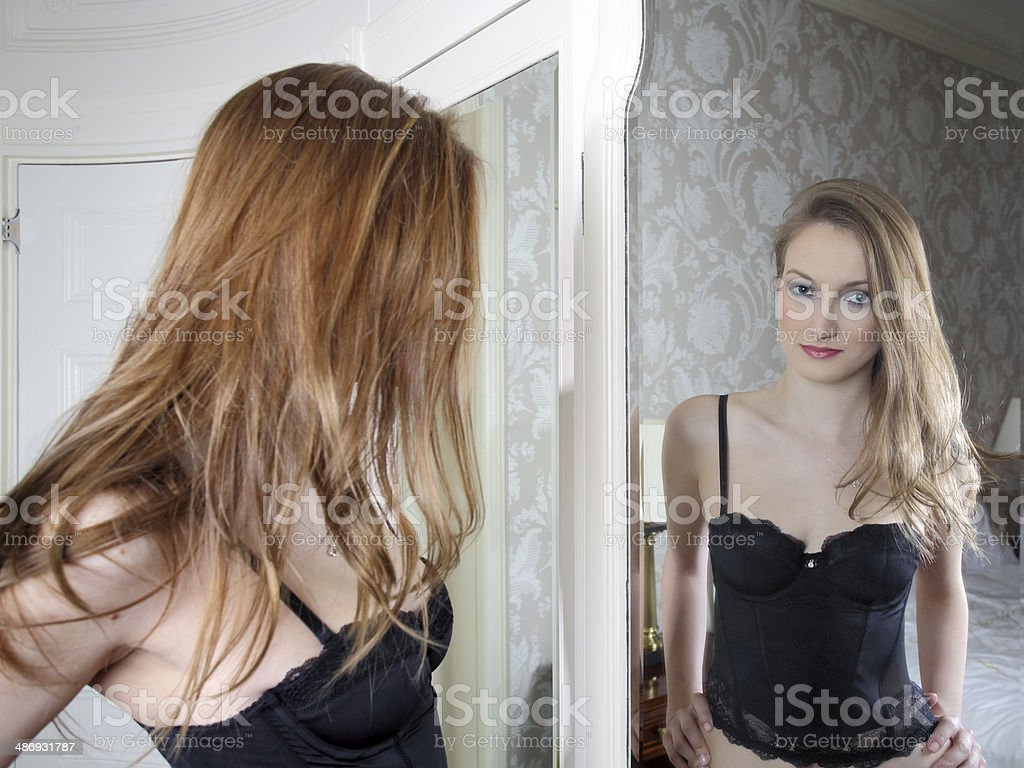 back view of an attractive woman in lingerie with reflection of her...