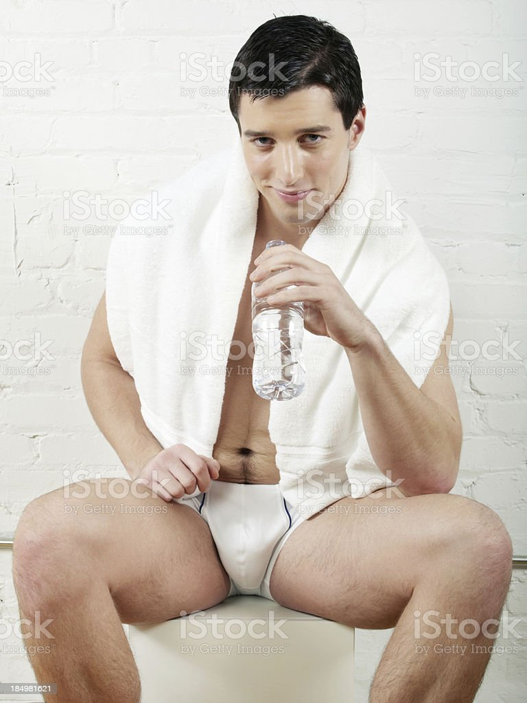 Sexy man in underwear drinking water relaxing after workout royalty-free stock photo