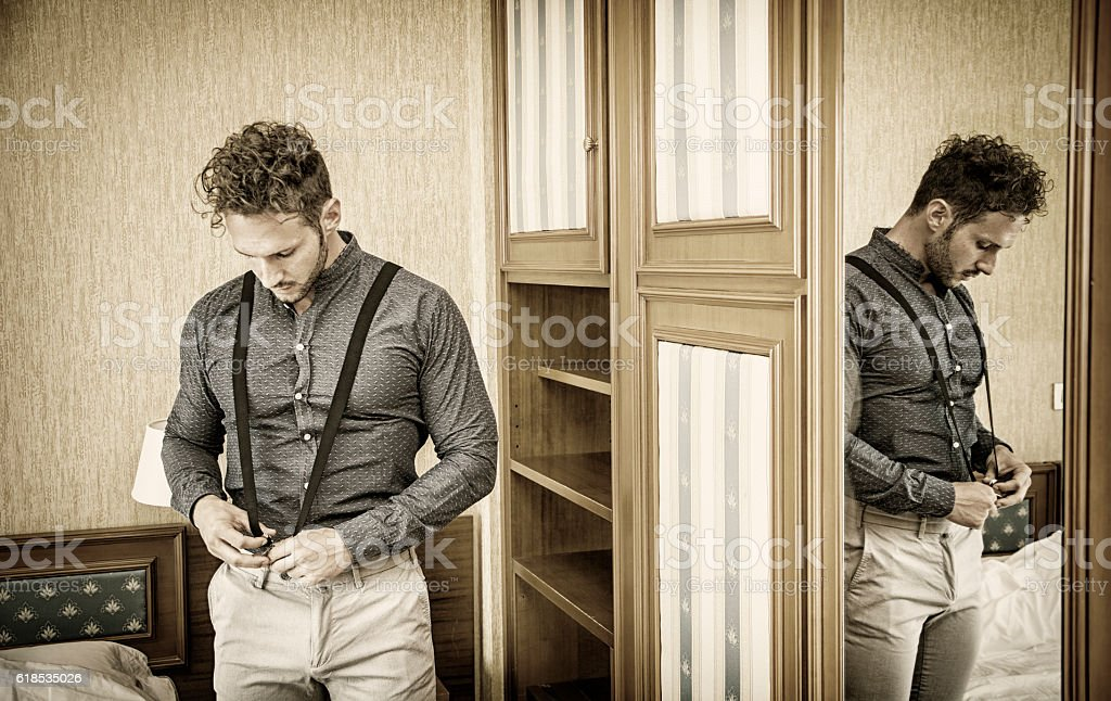 Sexy man standing and dressing in bedroom stock photo