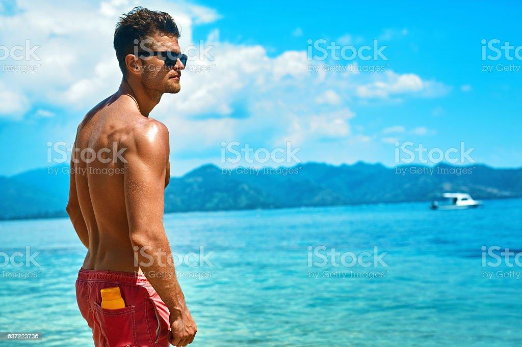 Sexy Man Tanning With Sunblock Skin Cream On Summer Beach. stock photo