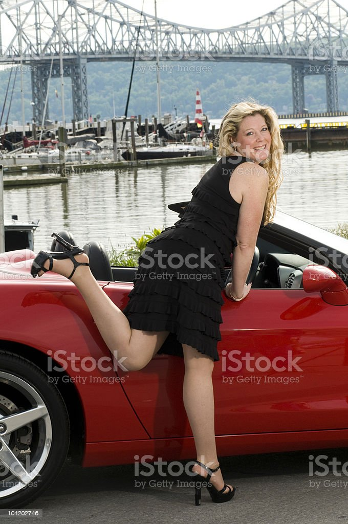 sexy middle age woman red sports car royalty-free stock photo