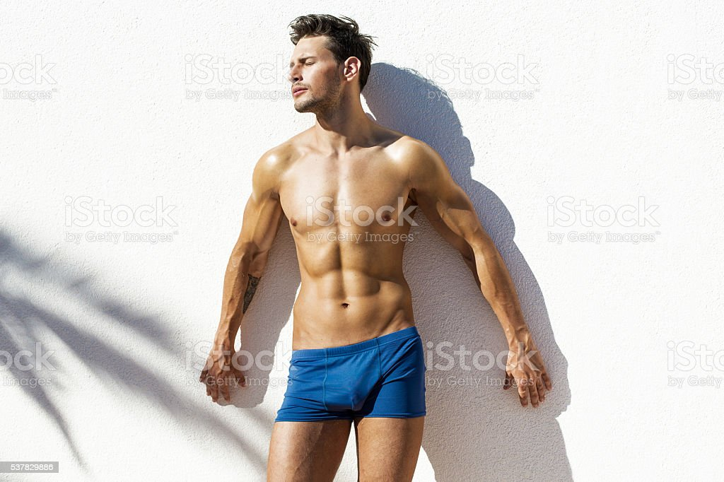 Sexy muscular model in beach shorts stock photo