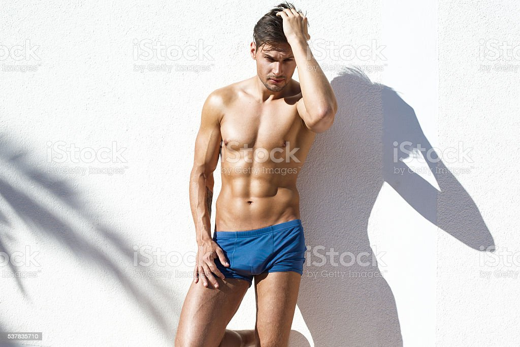 Sexy naked model with athetic body wearing blue beach shorts stock photo