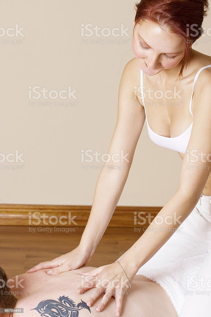 Sexy redhead giving massage to man stock photo