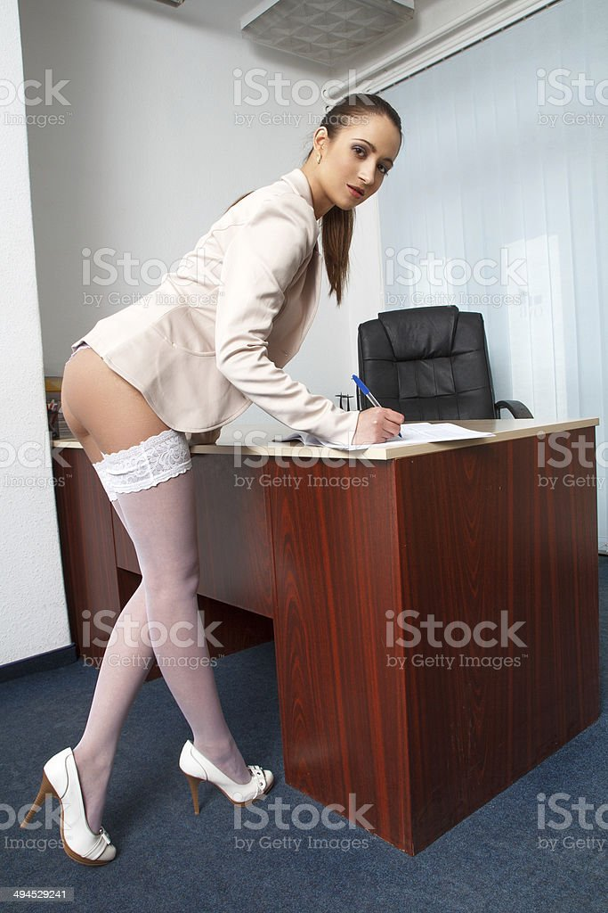 Sexy secretary in office writing with pen royalty-free stock photo