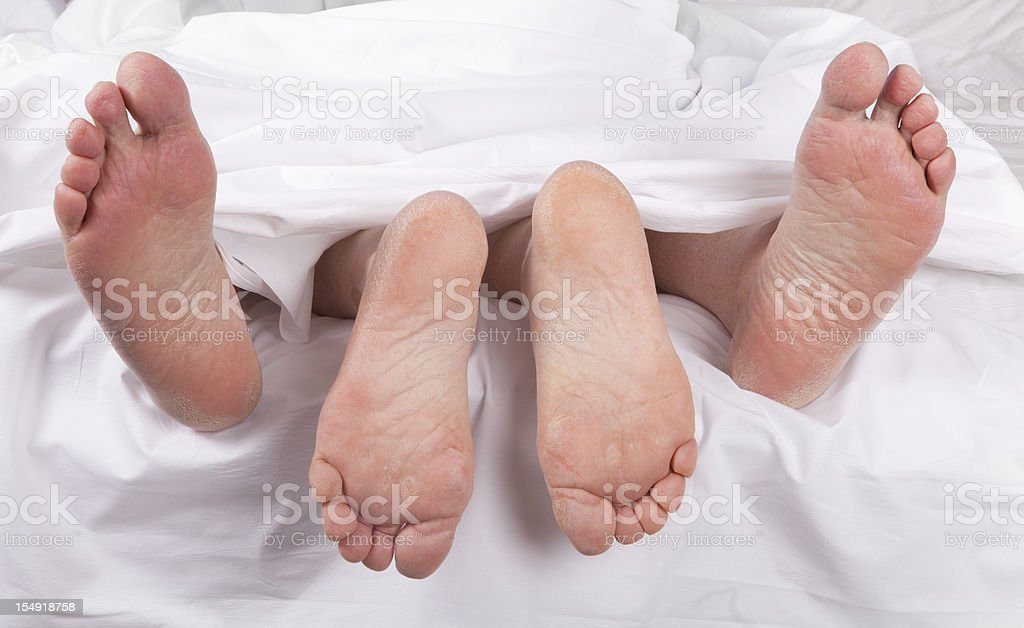 sexy senior feet in bed stock photo