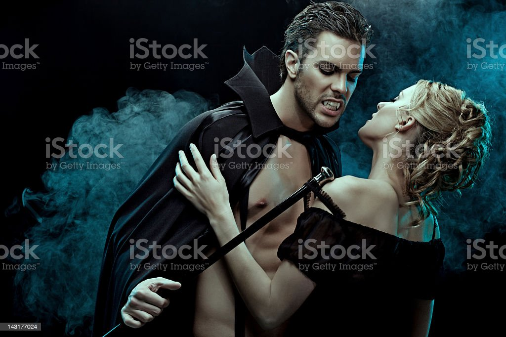 sexy vampire undressing his victim stock photo