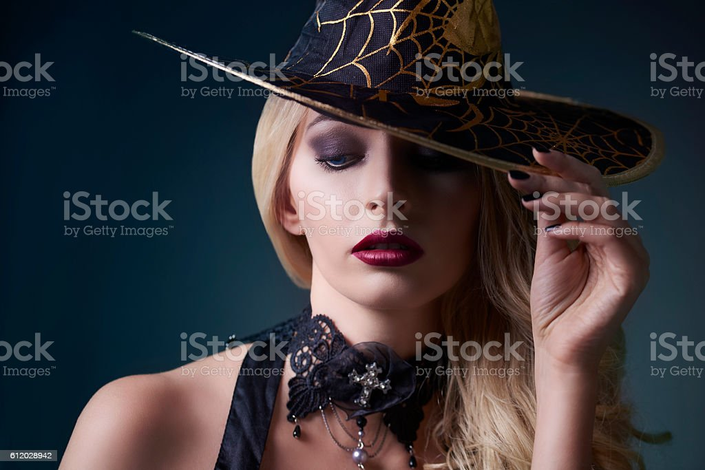 Sexy witch posing with hat stock photo