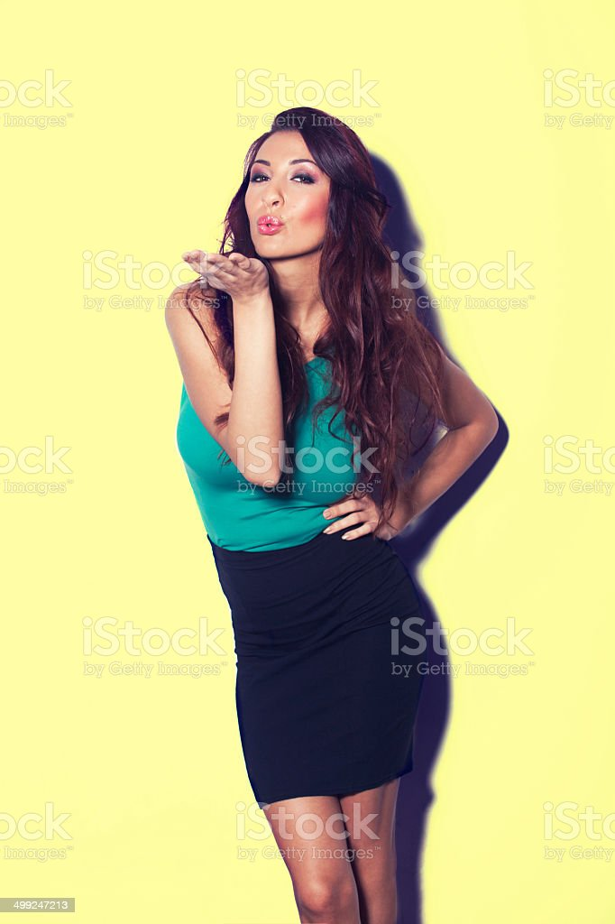 Sexy woman blowing a kiss on yellow background stock photo