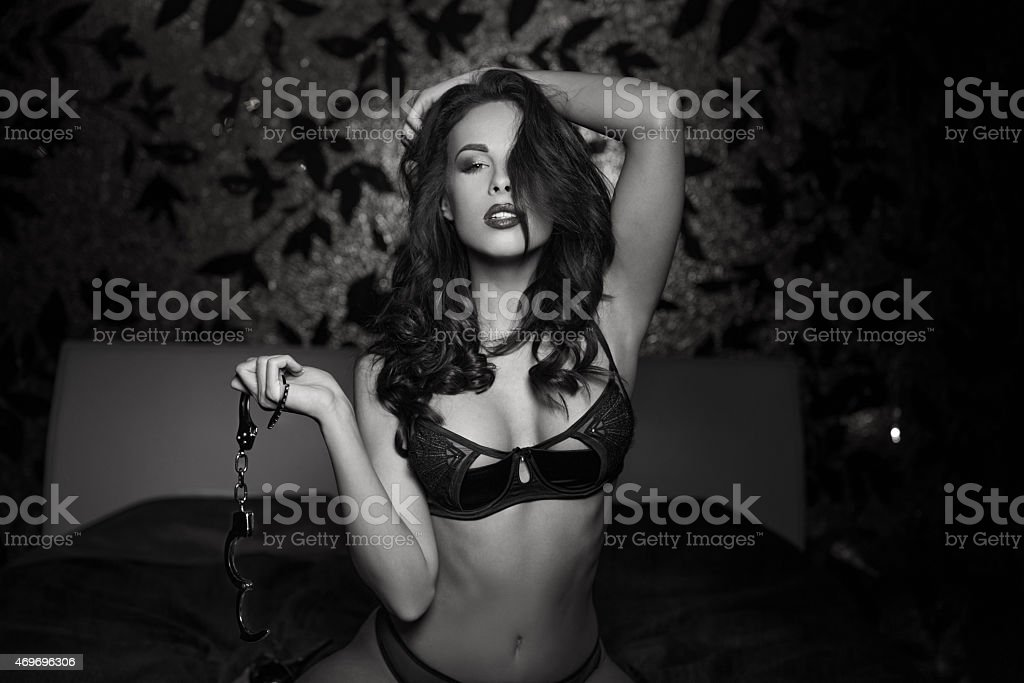 Sexy woman holding handcuffs black and white stock photo