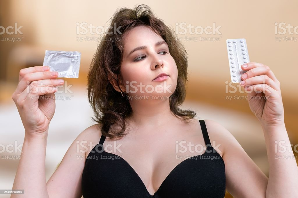 Sexy woman holds condom and contraceptive hormonal pills. Anticonception comparison. stock photo