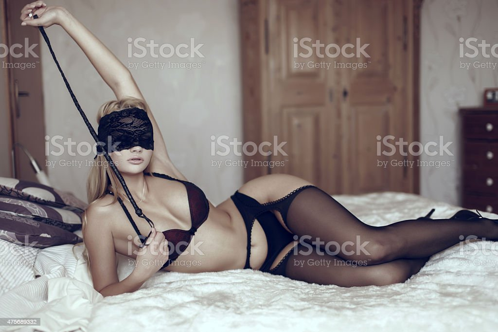 Sexy woman in lace eye cover with whip stock photo