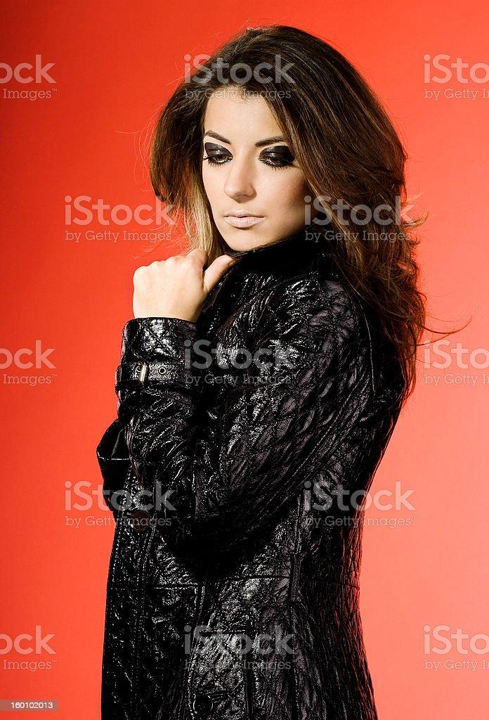Mulher sexy em cabedal sobretudo sobre Fundo vermelho foto de stock royalty-free