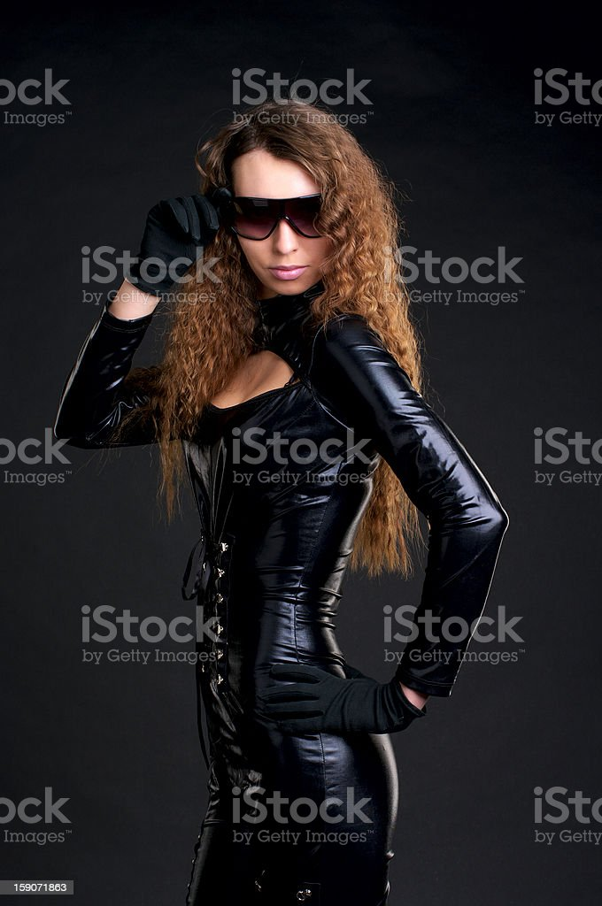 Sexy woman in skintight latex and sunglasses stock photo