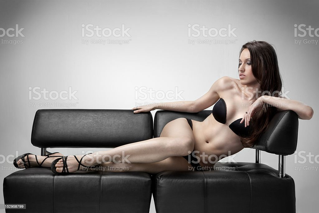 sexy woman in swimsuit lies on the sofa royalty-free stock photo