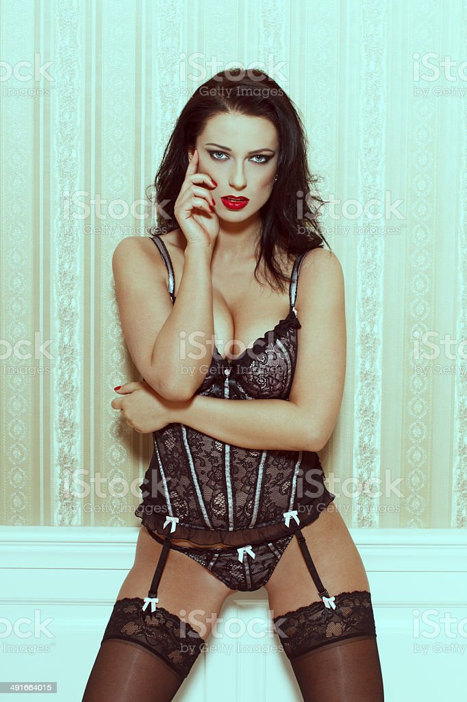 Sexy woman in underwear posing at vintage wall royalty-free stock photo