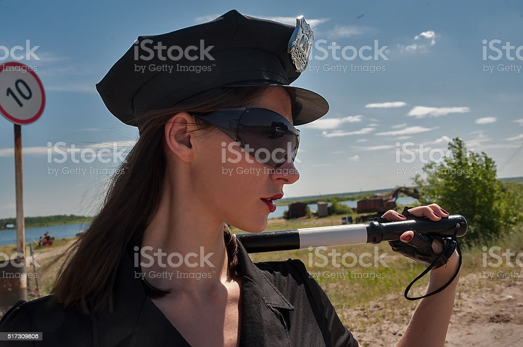 Sexy woman in uniform holding stick stock photo