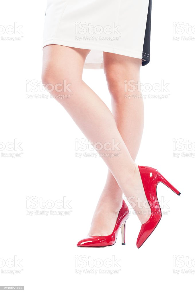 Sexy woman legs crossed wearing high heel red shoes stock photo