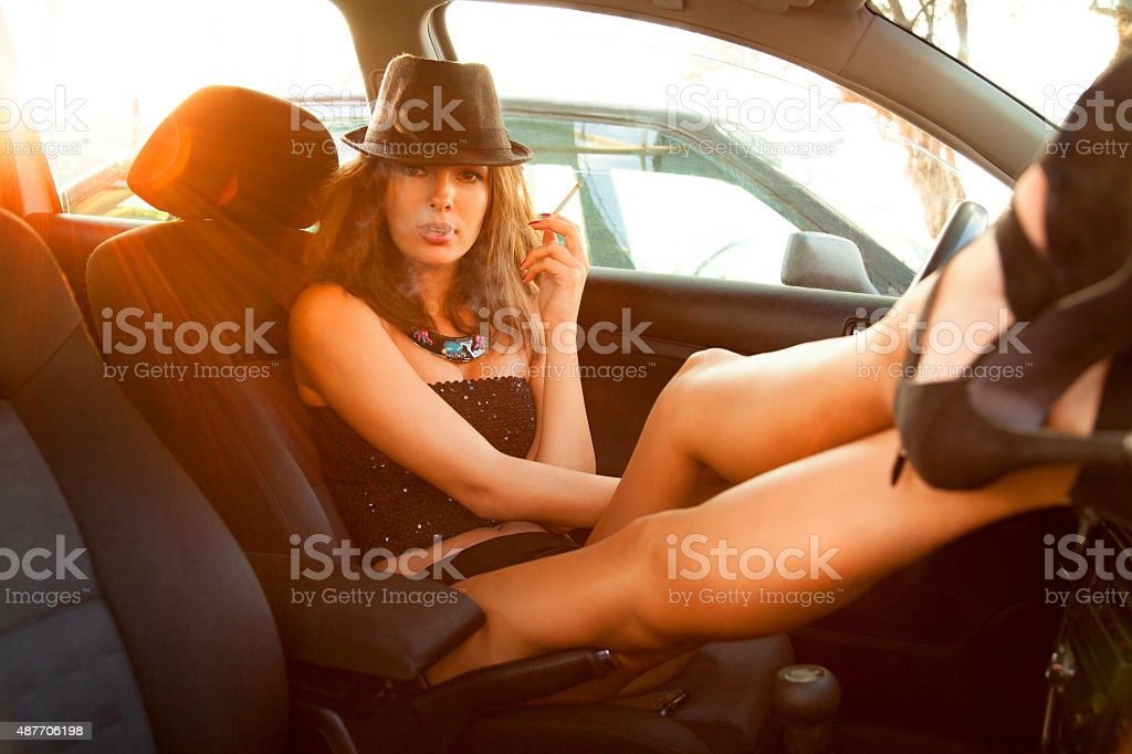 Sexy woman posing in the car stock photo