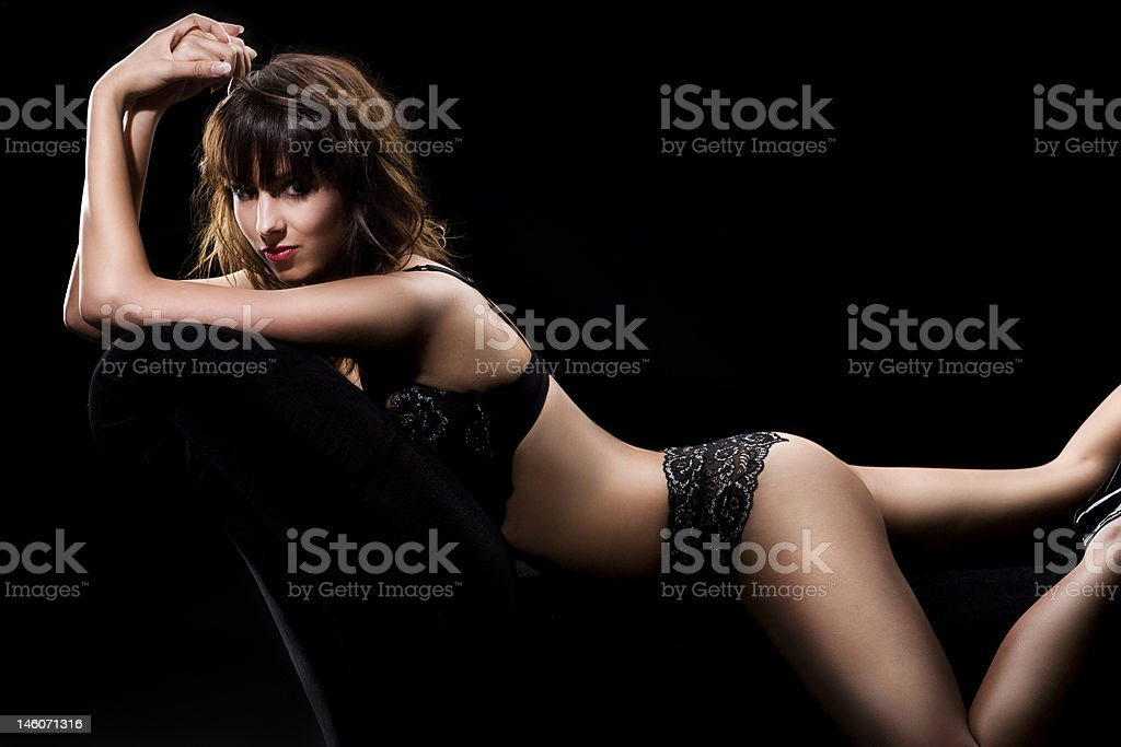 Sexy woman posing on couch in lingerie royalty-free stock photo