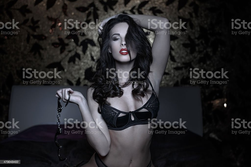 Sexy woman posing with handcuffs in bed stock photo