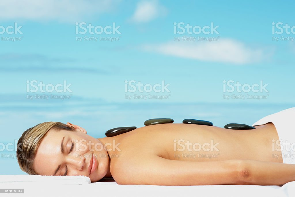 Sexy woman receiving hot stone treatment against sky royalty-free stock photo