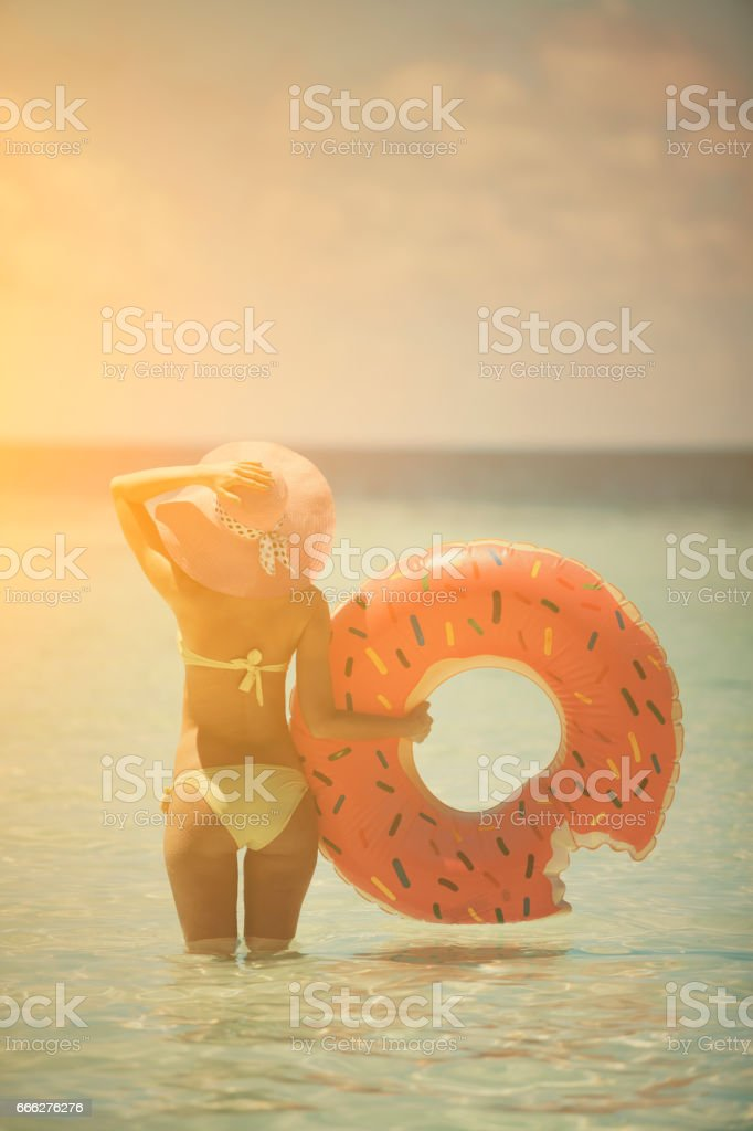 Sexy woman standing in the water with doughnut float, Maldives stock photo