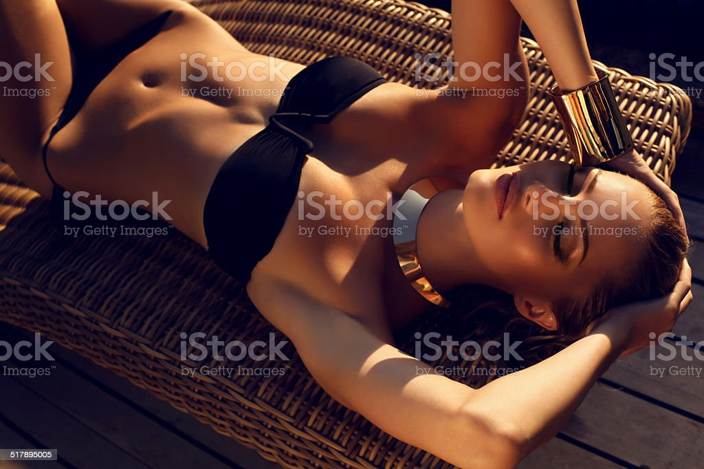 sexy woman with blond hair in bikini relaxing on beach stock photo