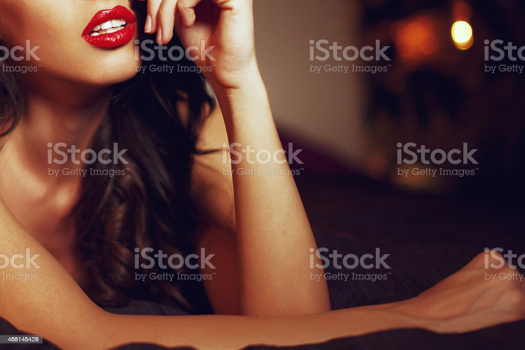 Sexy woman with red lips on bed closeup stock photo