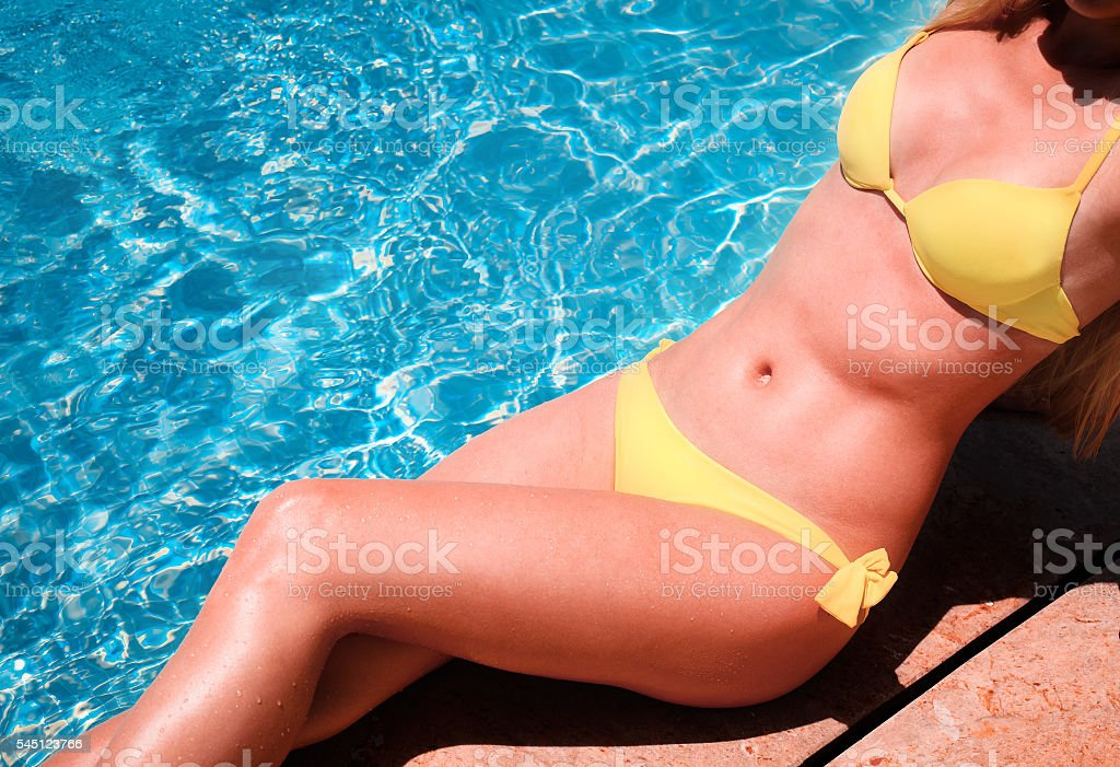 Sexy young blond woman posing in a yellow bikini stock photo