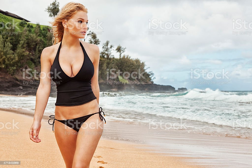 Sexy Young Blonde Woman in Black Tankini Walking on Beach stock photo