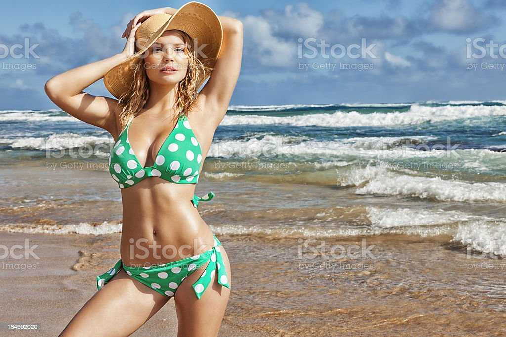 Sexy Young Blonde Woman in Green Polka-dot Bikini and Hat stock photo