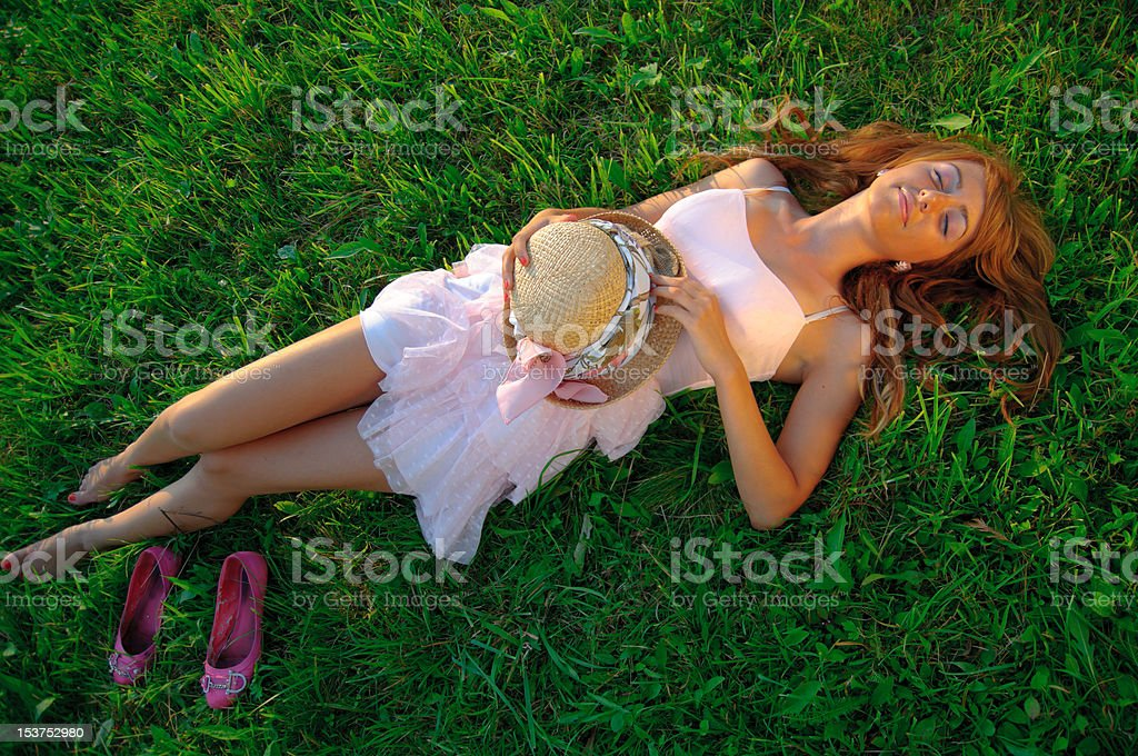 Sexy young girl lying down on grass royalty-free stock photo