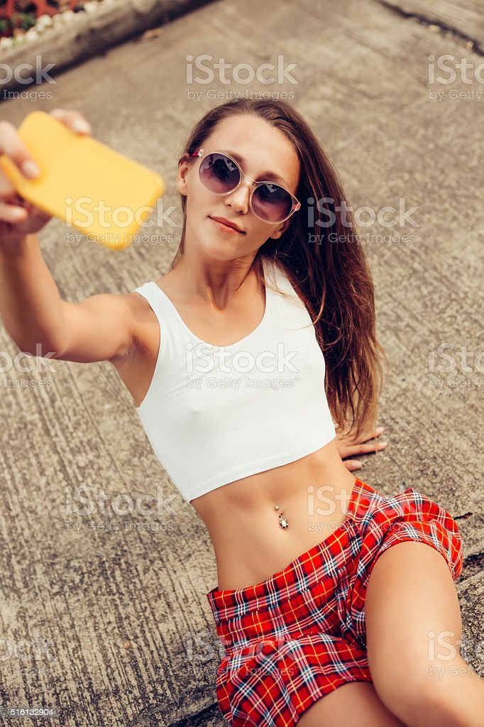 sexy young lady in mini skirt makes selfie on phone stock photo