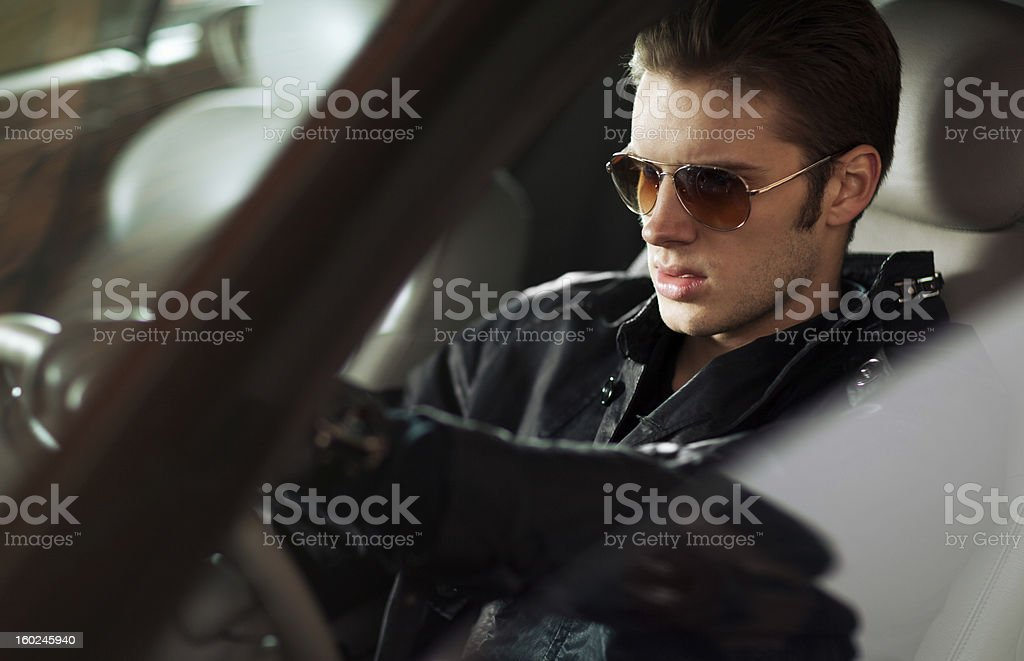 Sexy young man driving car stock photo