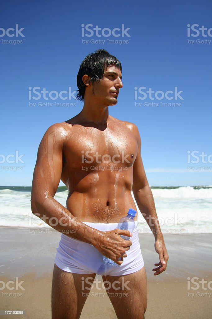 Sexy Young Man on the Beach with a Water Bottle royalty-free stock photo
