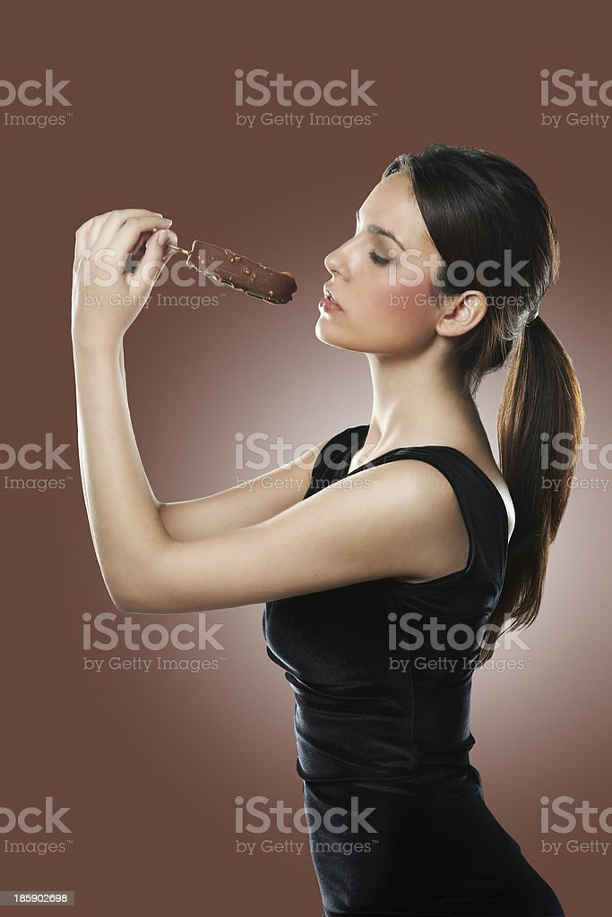 Sexy young woman eating ice cream over brown background royalty-free stock photo