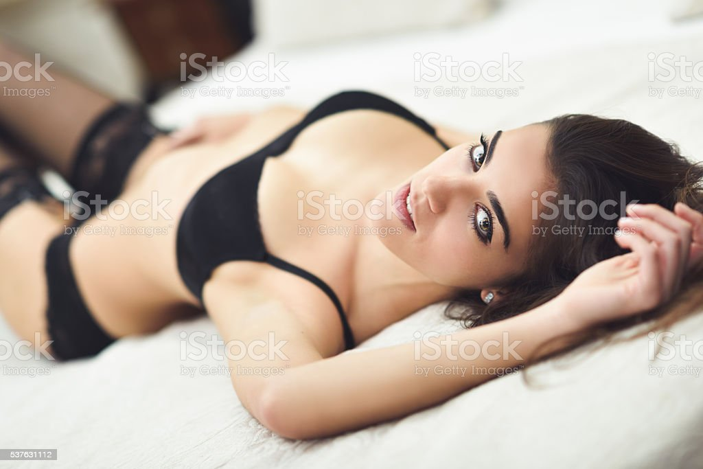 Sexy young woman in lingerie posing on the bed stock photo