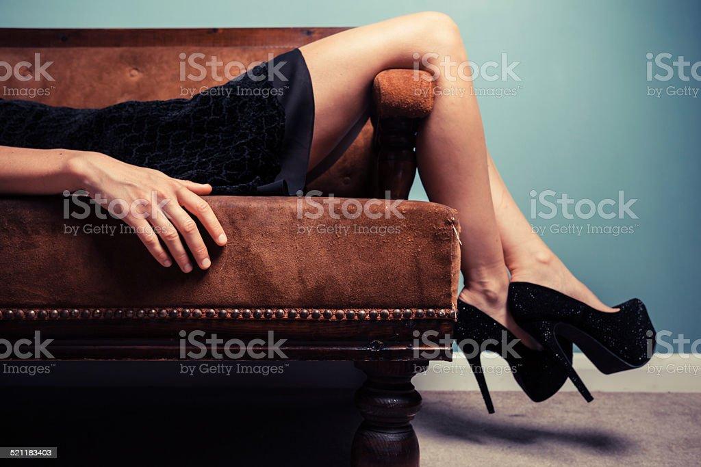 Sexy young woman lying on sofa stock photo