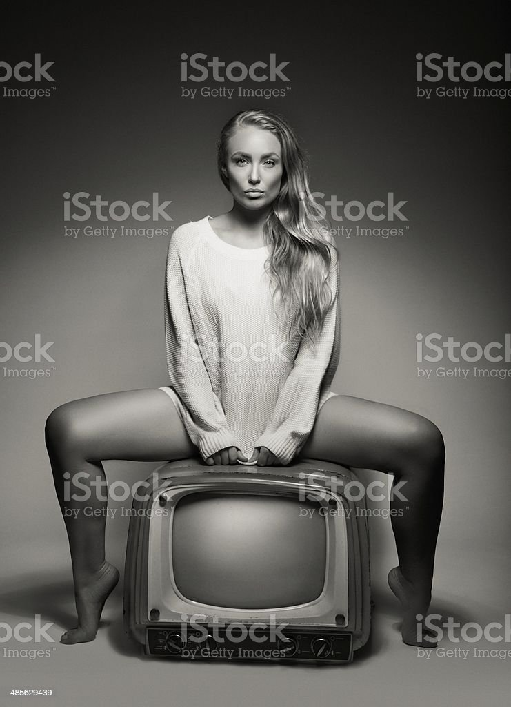 Sexy young woman sitting on a TV stock photo
