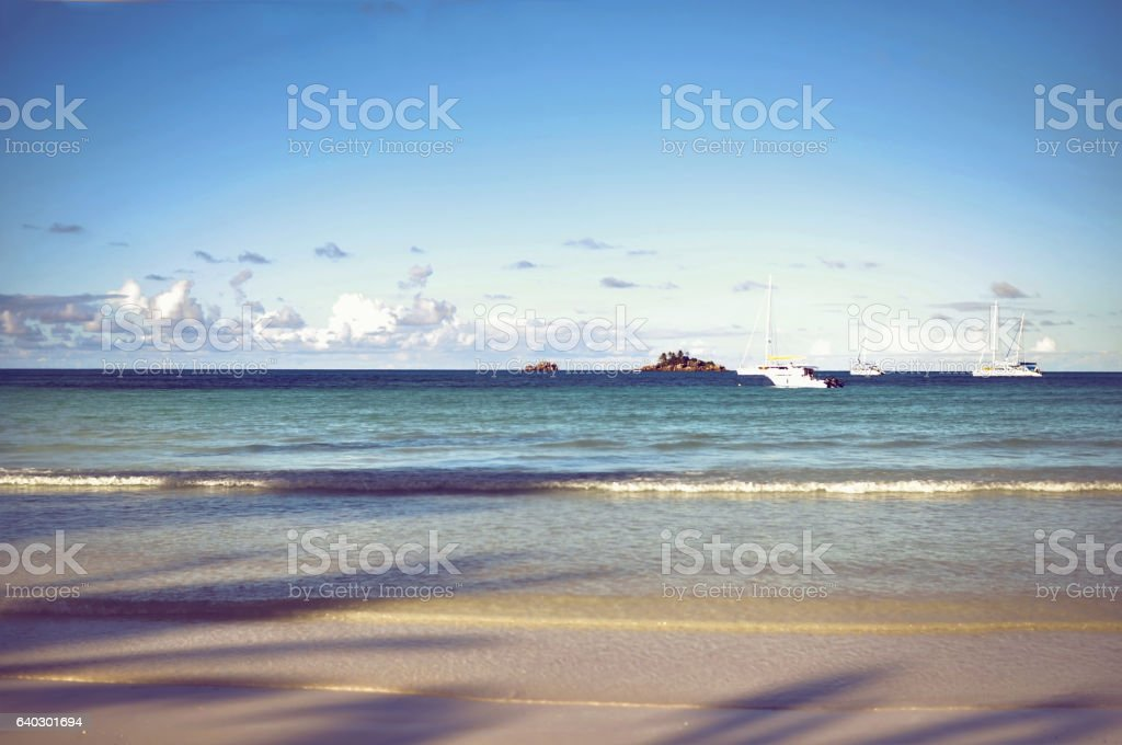 Seychelles Praslin island seascape with calm ocean and yachts stock photo