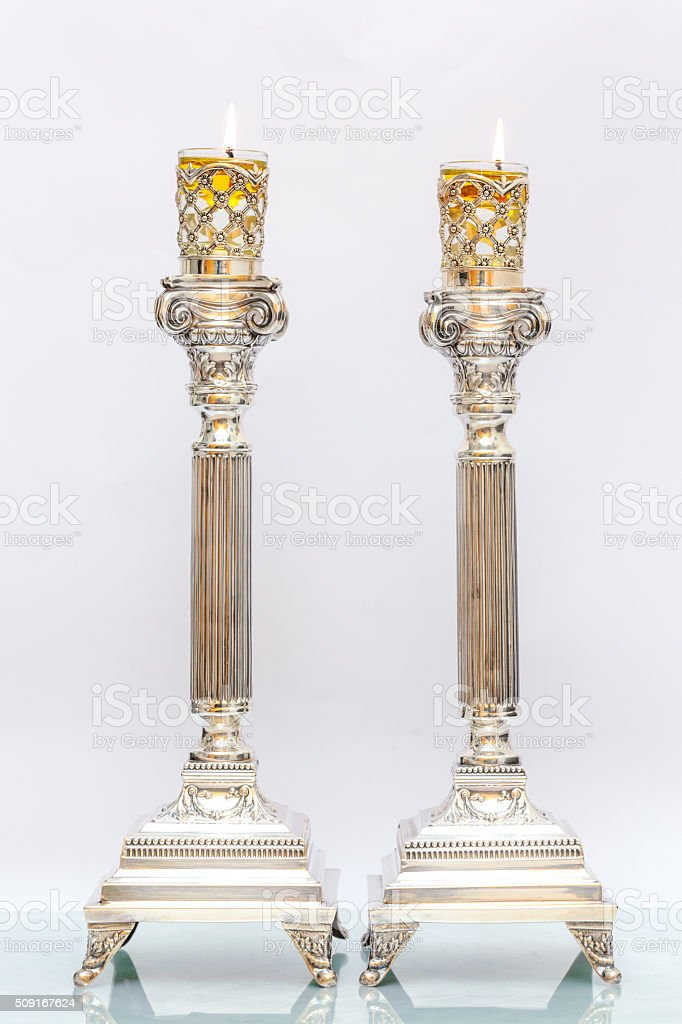 Shabbat candles. Silver candlesticks with olive oil. Light background stock photo