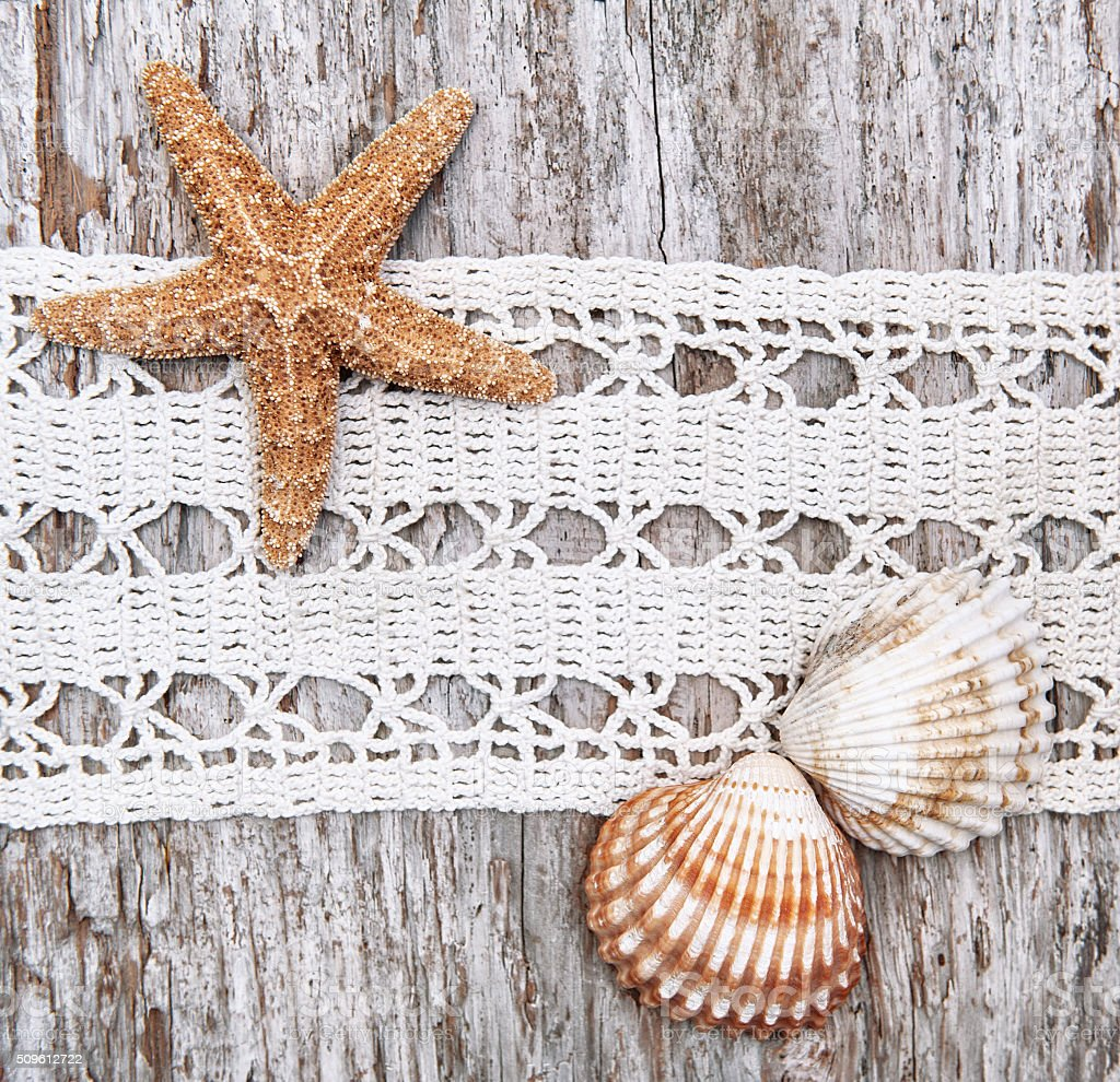 Shabby chic background with seashells and lace on old wood stock photo