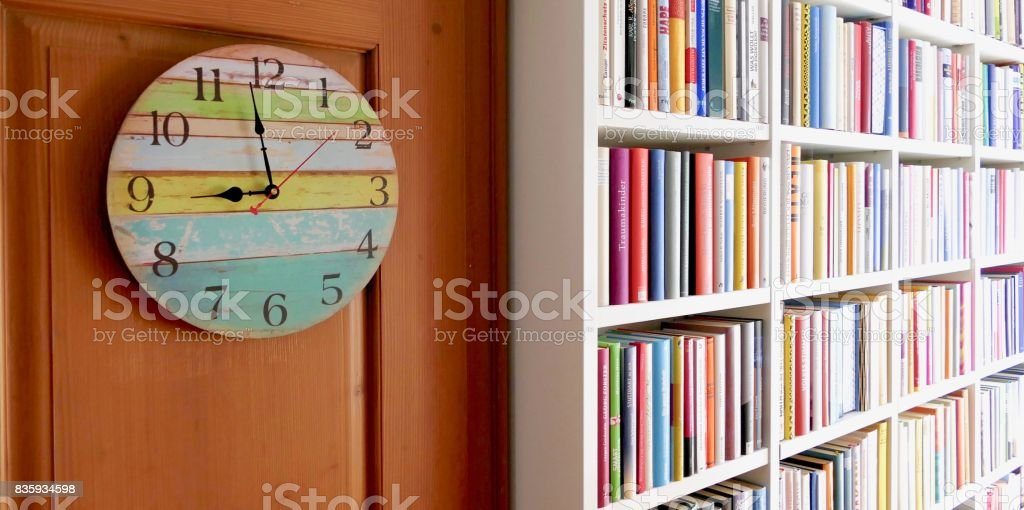 Shabby chick wall clock and white library book shelves packed with colorful books stock photo