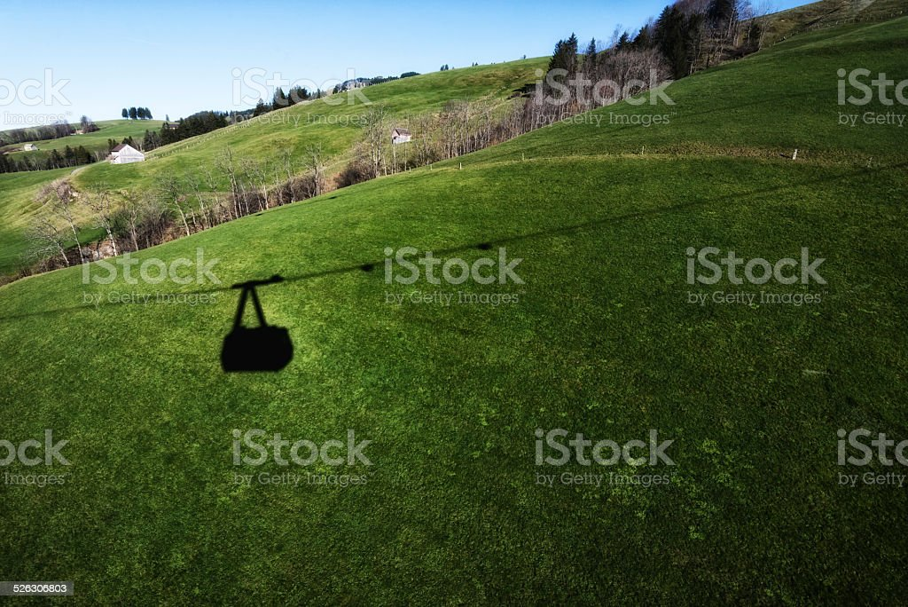 Shaddow of overhead Cable Car in the swiss landscape stock photo
