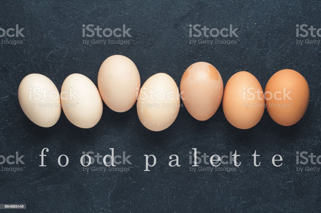 Shades of chicken eggs. The eggs flat lay on the dark concrete background stock photo