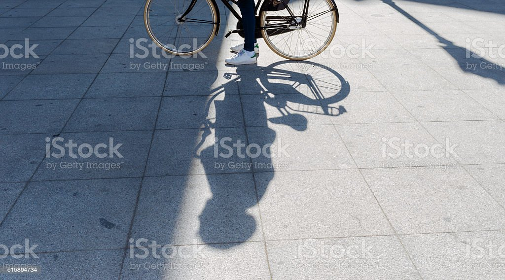 Shadow and Light of a Man with his Bike stock photo