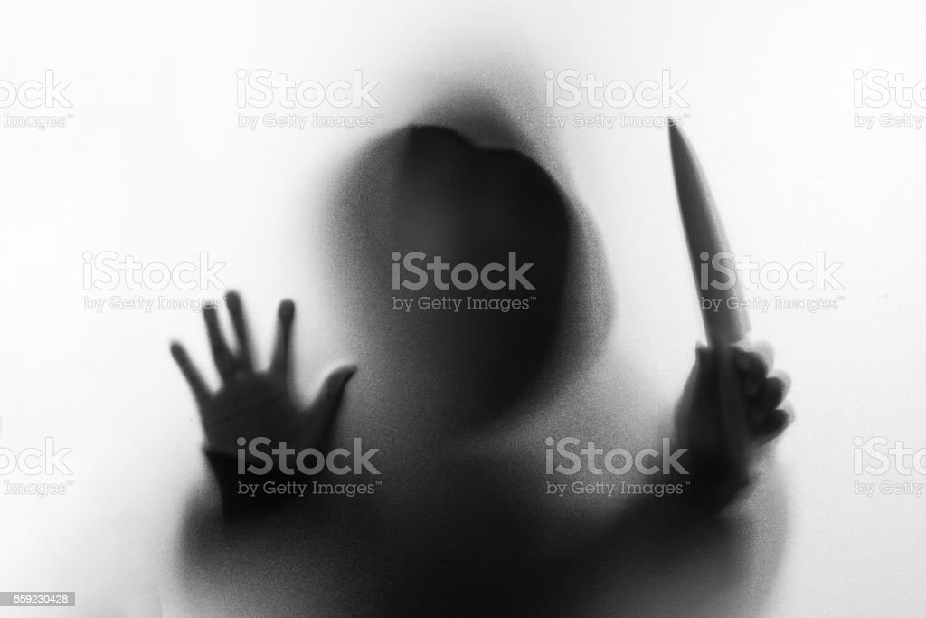 Shadow blur of horror man in jacket with hood knife in his hand.Dangerous man behind the frosted glass.Mystery man.Halloween background.Black and white picture.Blur picture. stock photo